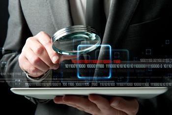 Detektiv mit Lupe und Tablet-PC